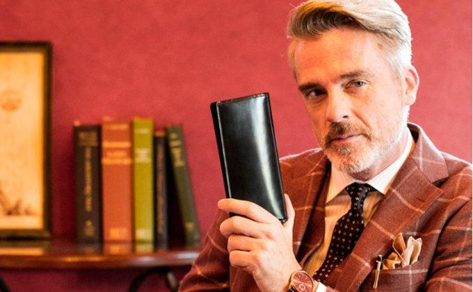 シェルコードバンの財布を持つ男性