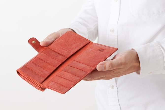 財布を開いてカード段を見せている男性