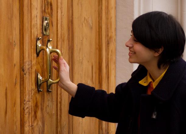 ドアを持ち笑うアヤメアンティーコのモデル女性