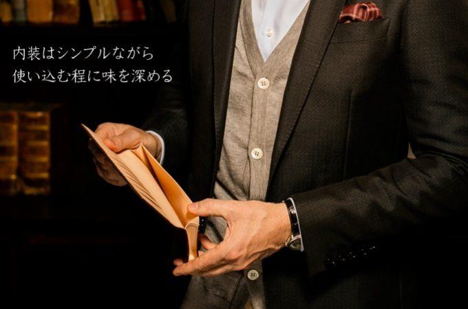 ココマイスターの小銭入れ無し長財布を持つ男性