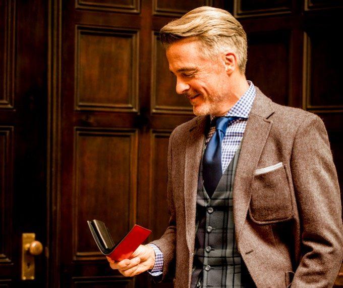 ココマイスターの赤い二つ折り財布を持つ男性