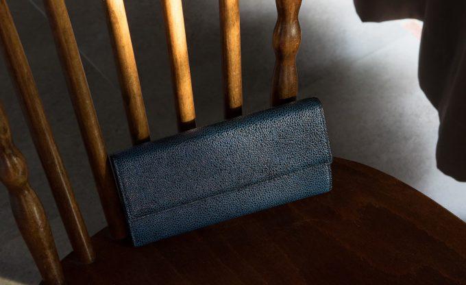 椅子に置いた漆塗りシボ型押しレザーカブセ長財布