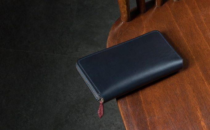 木の椅子の上に置いてあるブリランテ✕リザードラウンドジップ長財布