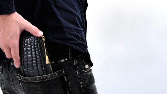 L字ファスナー長財布をポケットにしまう男性