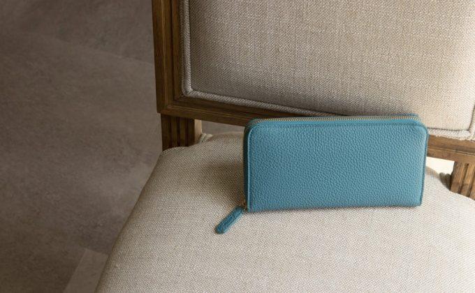 椅子の上に置いてあるシュランケンカーフラウンドジップ長財布