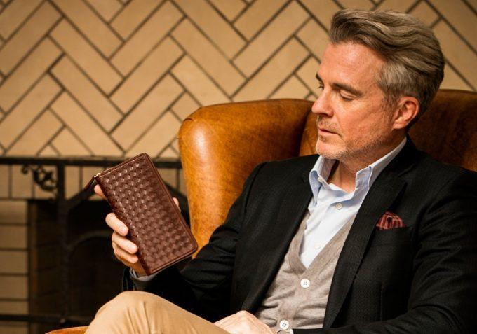 ボッテガヴェネタ以外の編み込みの財布を持つ男性