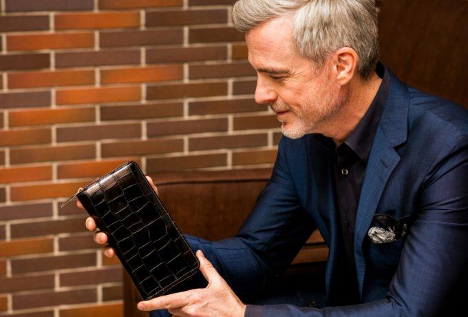 クロコダイル革財布を持って嬉しそうな男性
