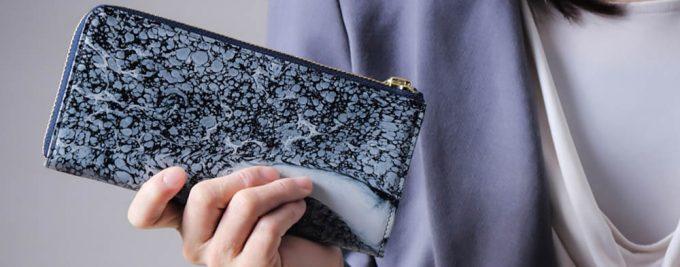 HANATORAのL字ファスナー長財布を持つ女性