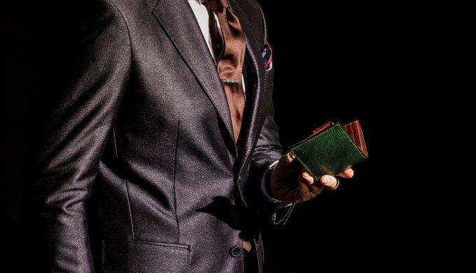 ロッソピエトラの二つ折り財布を持つ男性