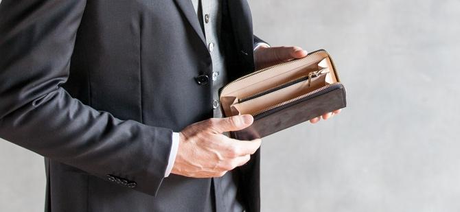 コードバンラウンド長財布を持つ男性