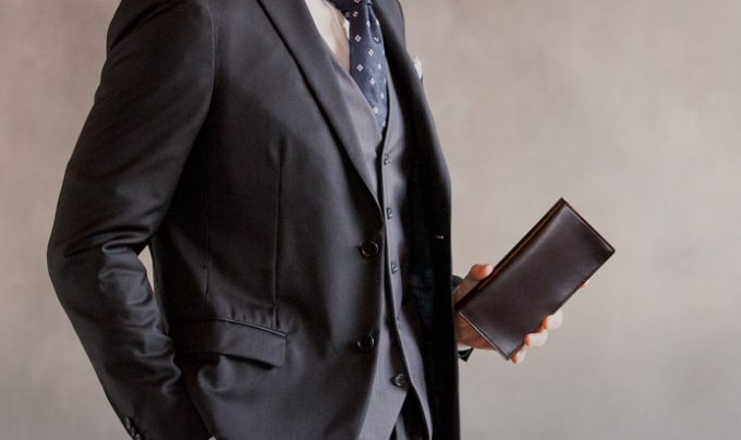コードバン通しマチ長財布を持つ男性