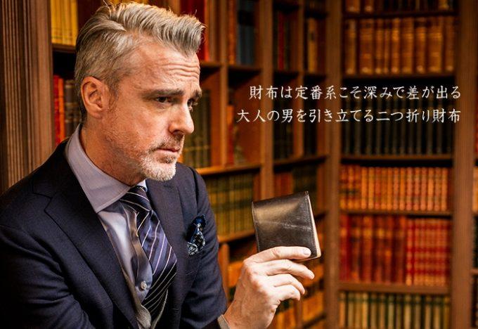 ブライドルレザーシリーズの二つ折り財布を持つ男性