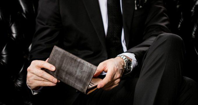 チャコールウッドのオークバークの財布を持つ男性モデル