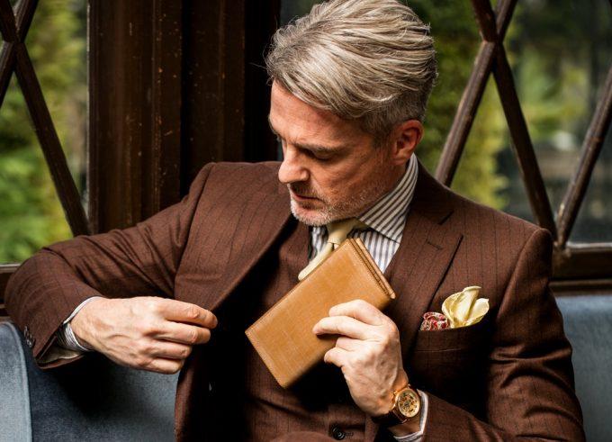 業界で一人勝ちと言われているココマイスターの財布をポケットにしまう男性