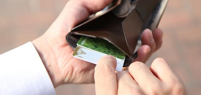 財布を握ってカードポケットからカードを出すところ