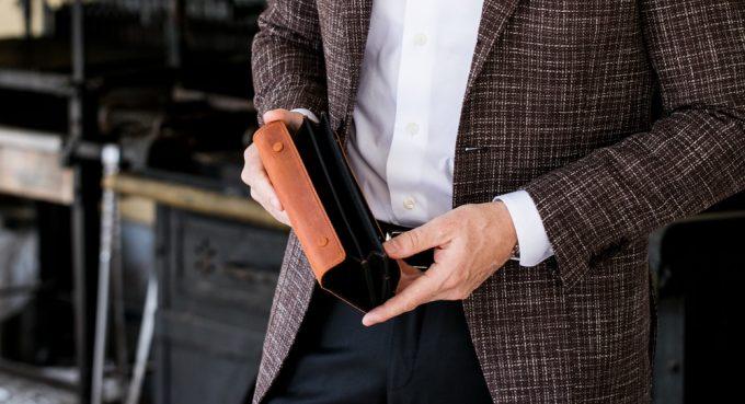 かぶせ長財布アレクサンダーウォレットを持つ男性