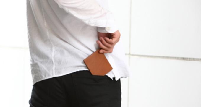 abrAsus薄いマネークリップをポケットにしまう男性