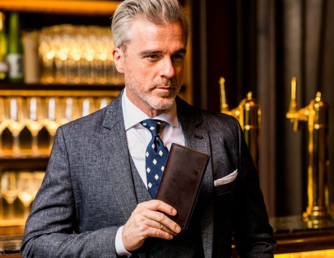 コードバンクラシック革財布を持つ男性