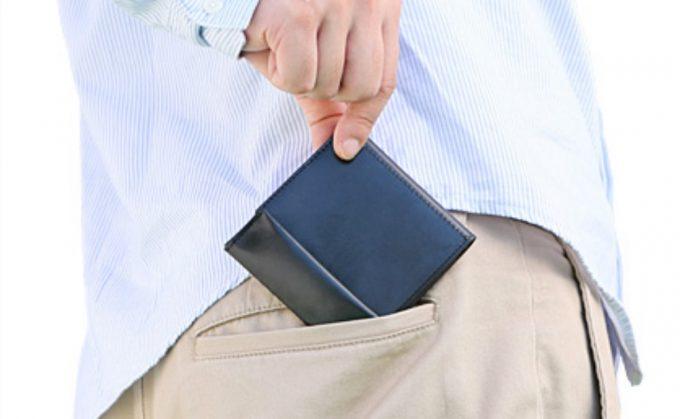 コンパクト財布をポケットに収める男性
