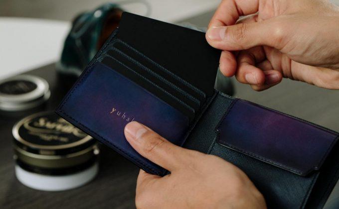 YVP132二つ折り財布からカードを取り出す人