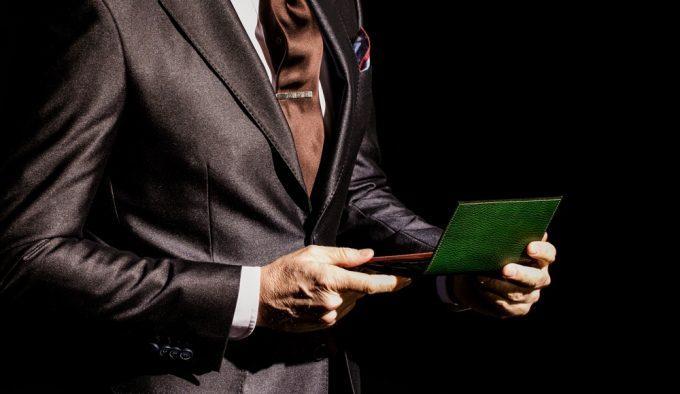 ココマイスターのロッソピエトラの財布を持つちょいワルオヤジ