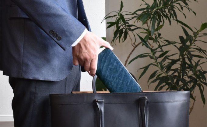 日本製象革ラウンドファスナー長財布をバックに入れる男性