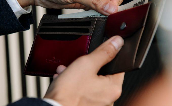 YFC131二つ折り財布からお札を出す人