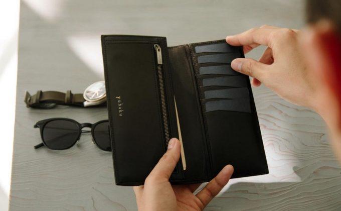 YLO130二つ折り財布からカードを出す男性