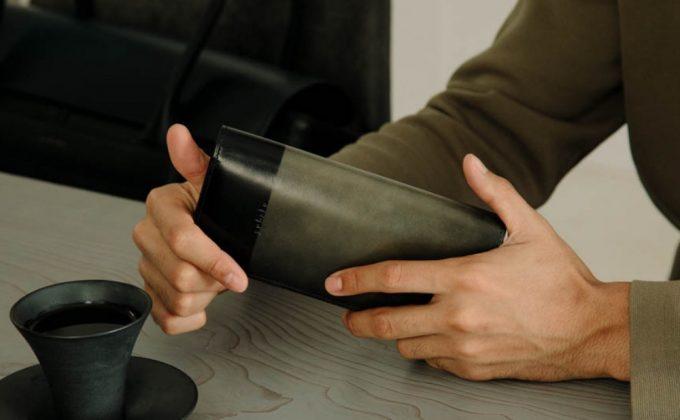 YLO110長財布(グレイカラー)を持つ男性