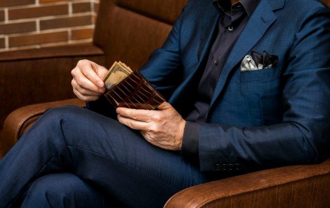 美しいセンター取りのクロコダイル革財布を持つ男性