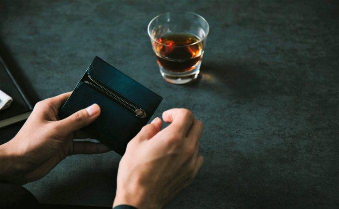 EVOシリーズの二つ折り財布を持つ男性