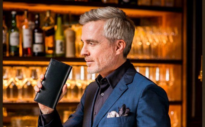 カヴァレオシリーズの革財布を持つ男性