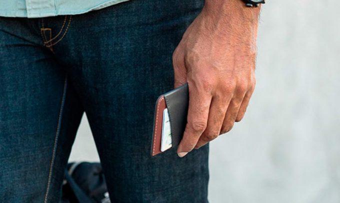 カードとお札だけ入る財布を持つ男性