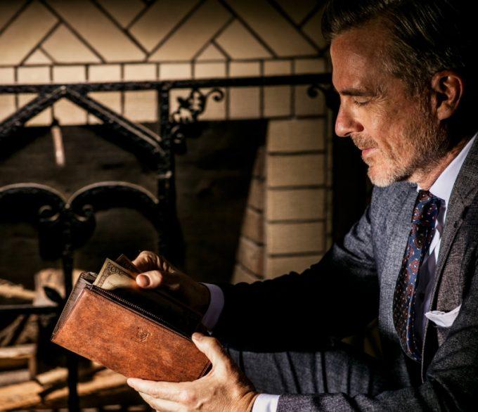 ベテルギウスシリーズの革財布を持つ男性