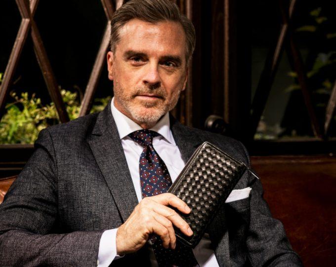 黒い財布を持つ格好良い男性
