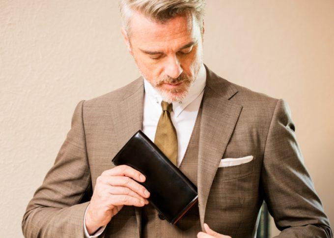 コードバンの革財布を懐へ入れるダンディーな男性
