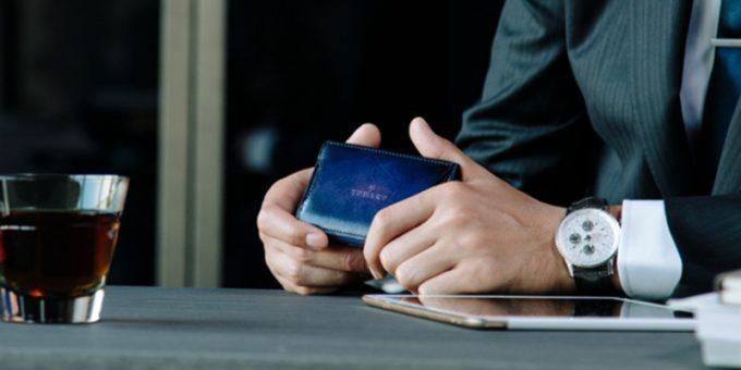外装カードポケット付きの財布を持つ男性