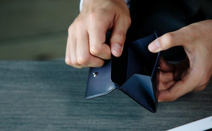 YVE150コインケースからカードを取り出す男性