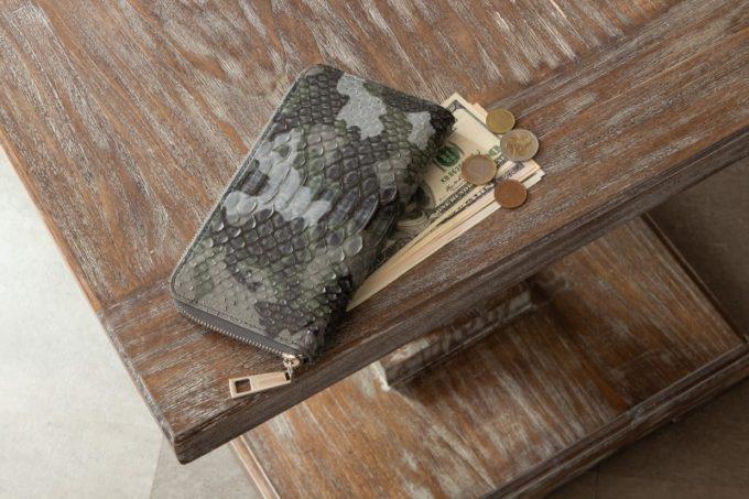 テーブルの上にお金と一緒に置いてあるパイソン フルオープンラウンドジップ長財布