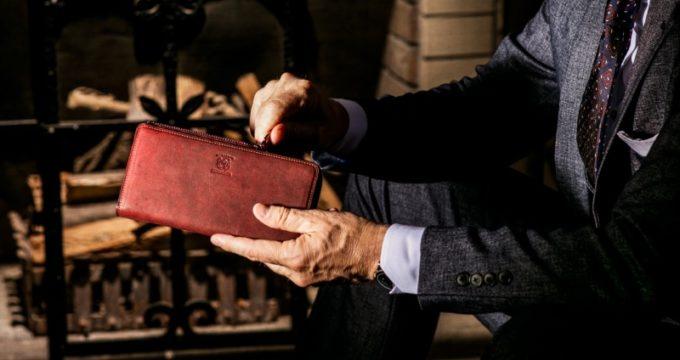 ココマイスターのL字ファスナー長財布を持つ男性