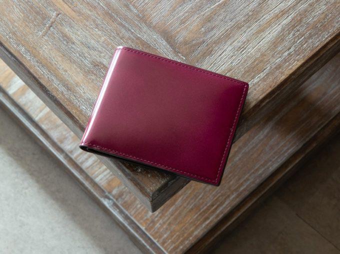 テーブルの上に置いてあるアーキライン二つ折り財布(艶有り)