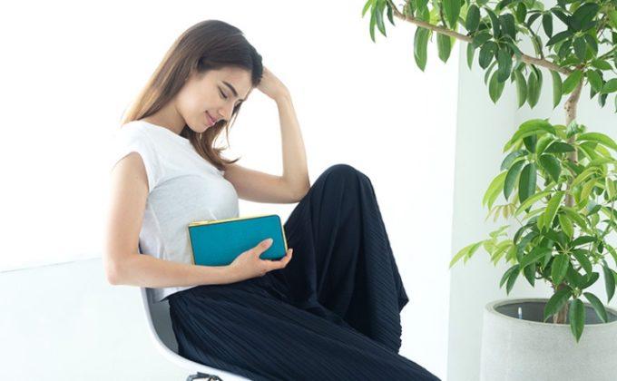 エイ革の財布を抱きかかえる美女