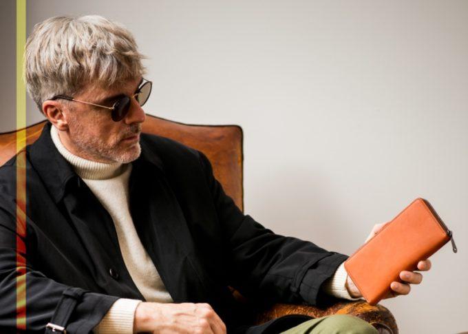 ラウンドファスナーウォレットを確認するサングラスを掛けた格好良い男性
