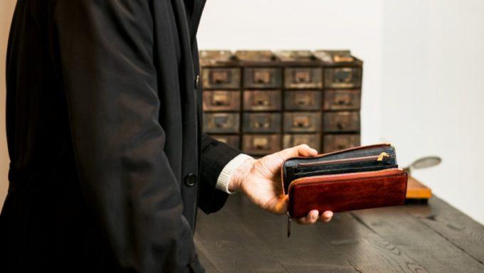 クラシカルな部屋でココマイスターの財布を持つ男性