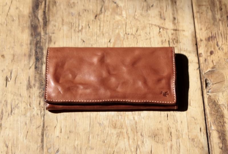 オリーブを加える鳩が外装に刻印されているsotの革財布