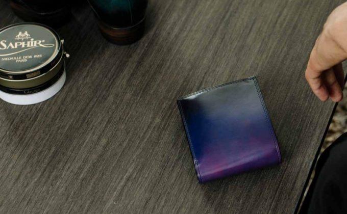 紫の二つ折り財布を手入れする男性