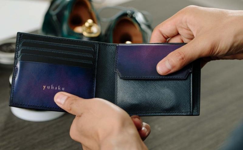 yuhakuの紫色の二つ折り財布を持つ男性