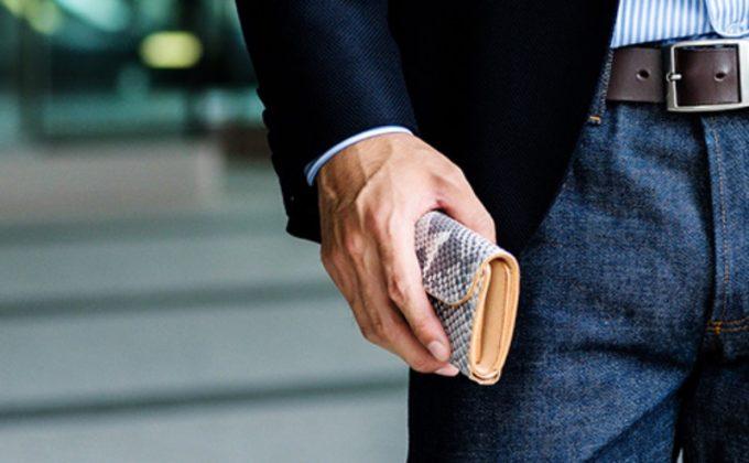 蛇革財布を持つ男性
