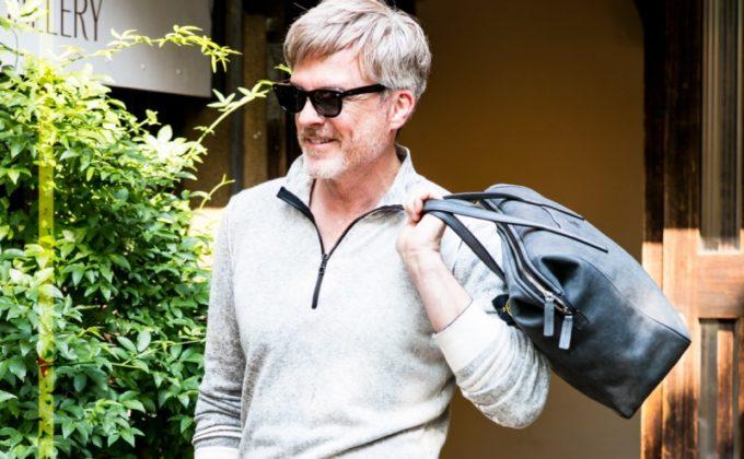 トート型鞄を片手で持ち笑う男性