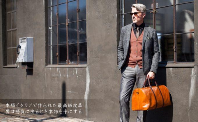 ボストンバッグを持ち立っている男性